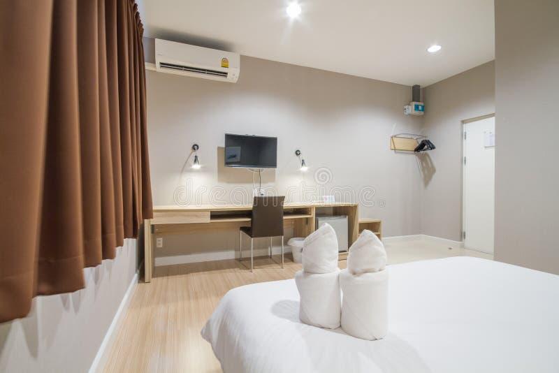 春武里市,泰国–2018年6月24日:在一张舒适的床上的白色毛巾与舒适卧室 库存照片