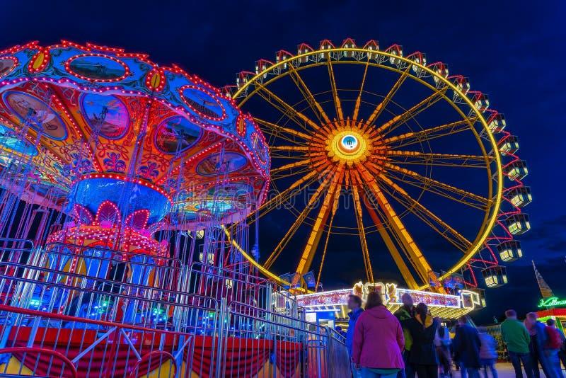 春节在慕尼黑在与一被照亮的弗累斯大转轮和链carusel的蓝色小时 库存照片