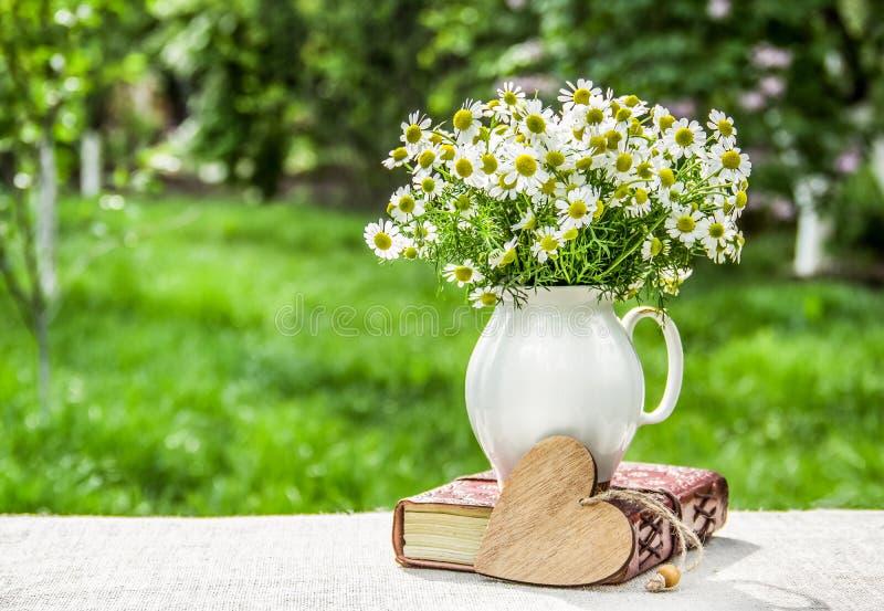 春黄菊花束在花瓶的 束雏菊和木心脏 自然庭院背景 免版税图库摄影