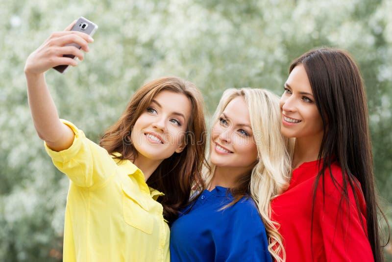 是三个美丽的女性的朋友现代的通过采取selfies 库存照片