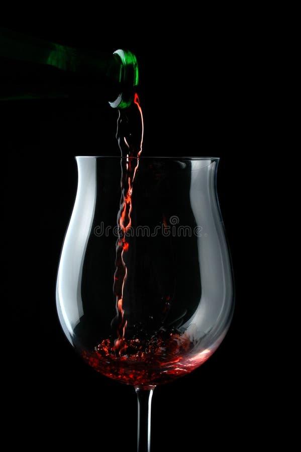 是下落玻璃倒的红葡萄酒 免版税库存图片