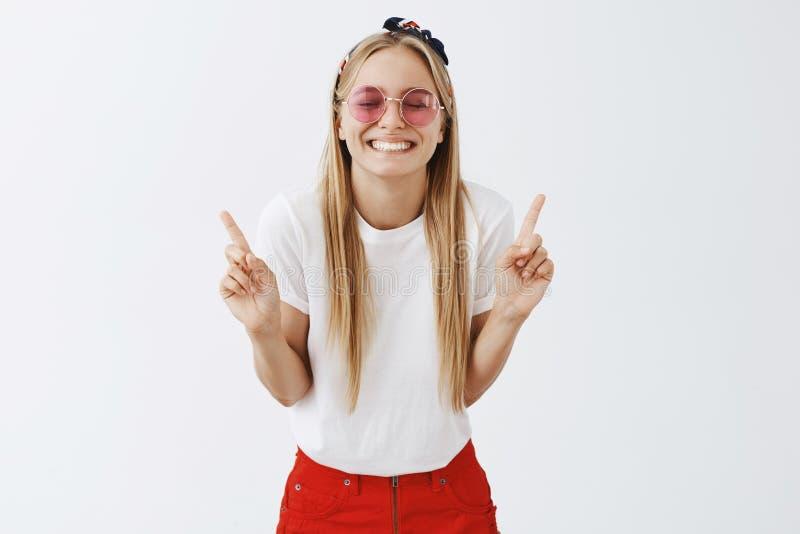 是什么的乐趣第一 咧嘴太阳镜和头饰带的乐观和嬉戏的年轻白肤金发的妇女画象  库存照片