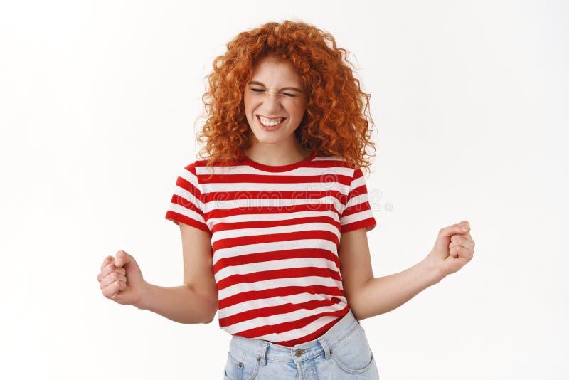 是令人敬畏 激动的愉快的红头发人卷曲年轻胜利的25s女孩紧握拳头胜利欢欣庆祝优秀 库存图片