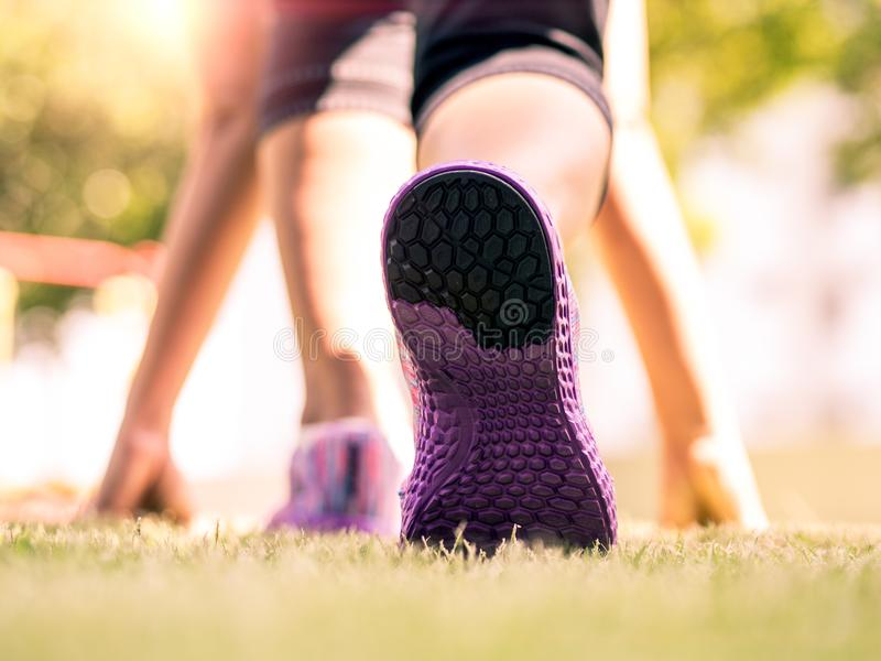 是准备好平稳 跑鞋特写镜头在草,小姐开始状态的和去的在公园跑 库存照片