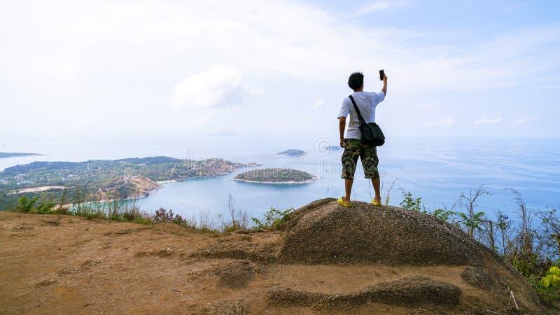 是在做在美好的自然视图的自然风景英俊的年轻人藏品智能手机的selfie时间selfie在普吉岛 库存照片