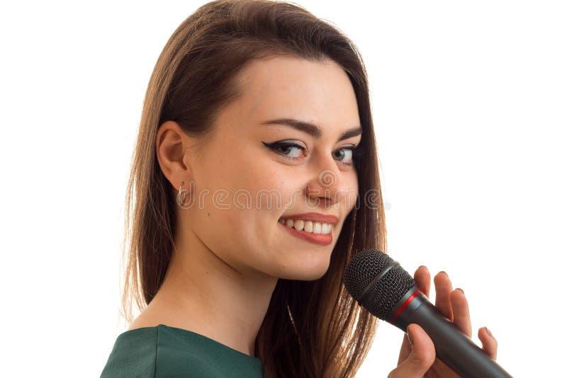 是微笑和拿着话筒一个卓越的女孩的特写镜头画象 库存图片