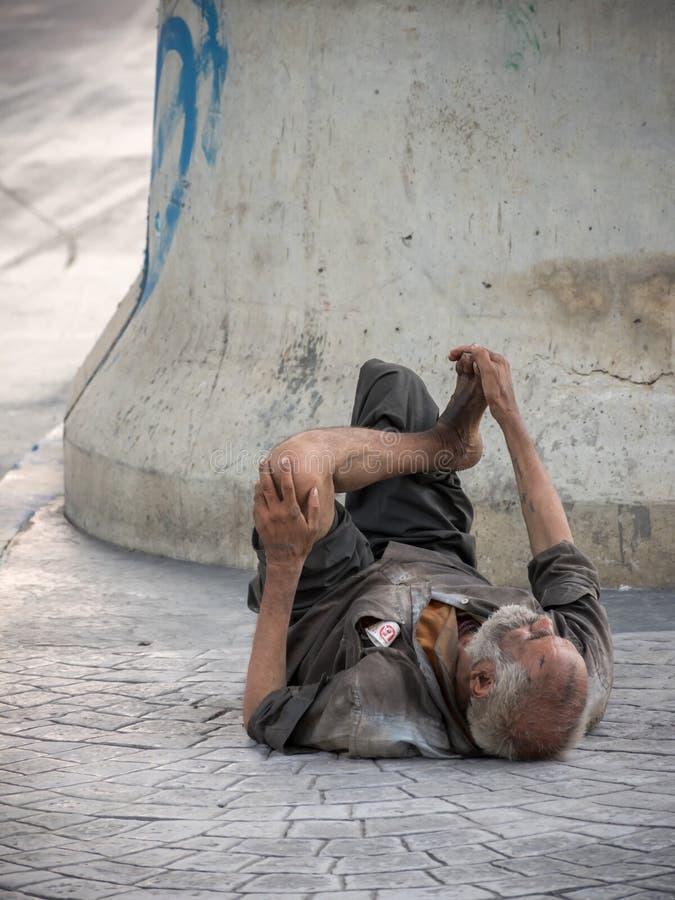 是无家可归或叫化子睡觉在街道旁边的一个老人 免版税库存照片