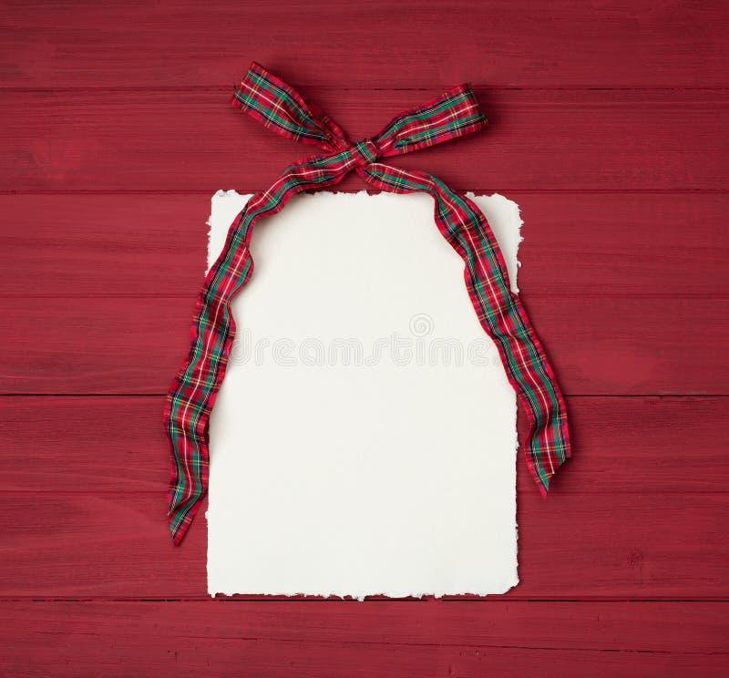 是有葡萄酒纸的红色和绿色格子花呢披肩与在土气木委员会背景的边缘与拷贝空间的圣诞节弓 免版税库存图片
