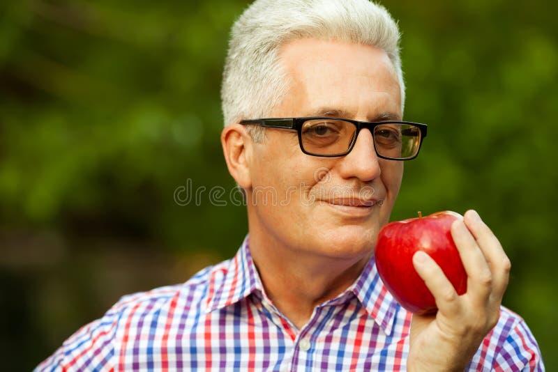是概念现有量有医疗保健帮助延迟药片 一个微笑的成熟人的画象用苹果 库存照片