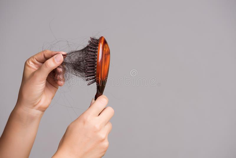 是概念现有量有医疗保健帮助延迟药片 妇女显示她的与长的损失头发和拉扯她的头发的刷子从刷子 免版税库存照片