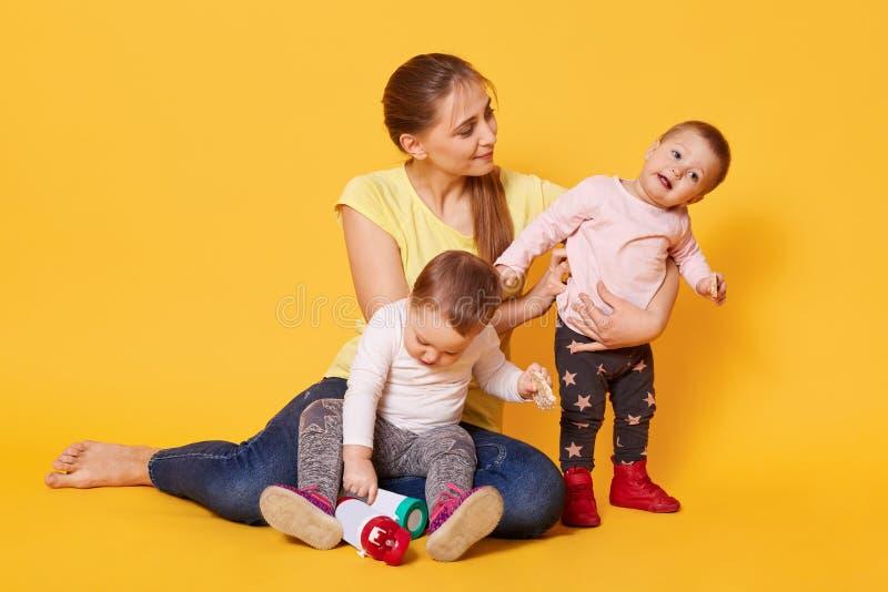 是活跃有同情心的母亲画象繁忙的与她喧闹的甜孩子,坐地板,亲切大气,戏剧比赛 免版税图库摄影