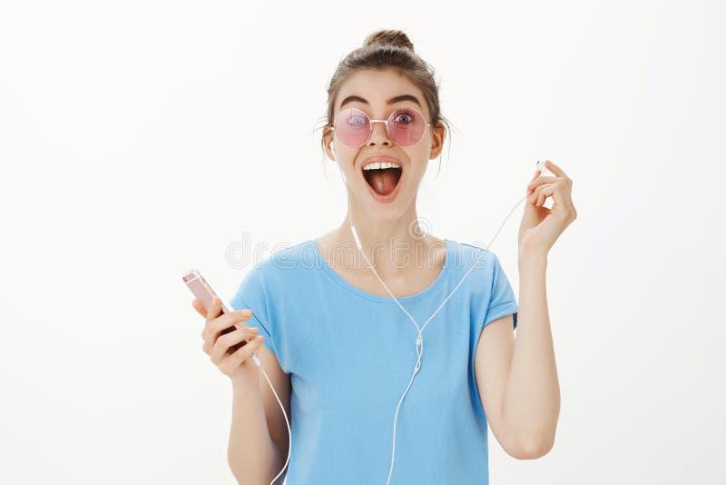是的女孩惊奇步行沿着向下街道和遇见老朋友,尖叫从幸福,离开耳机和 免版税库存图片