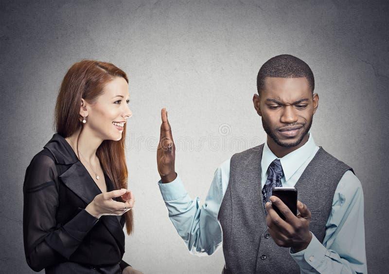 是的妇女看智能手机的被忽略的路过的英俊的人 库存图片