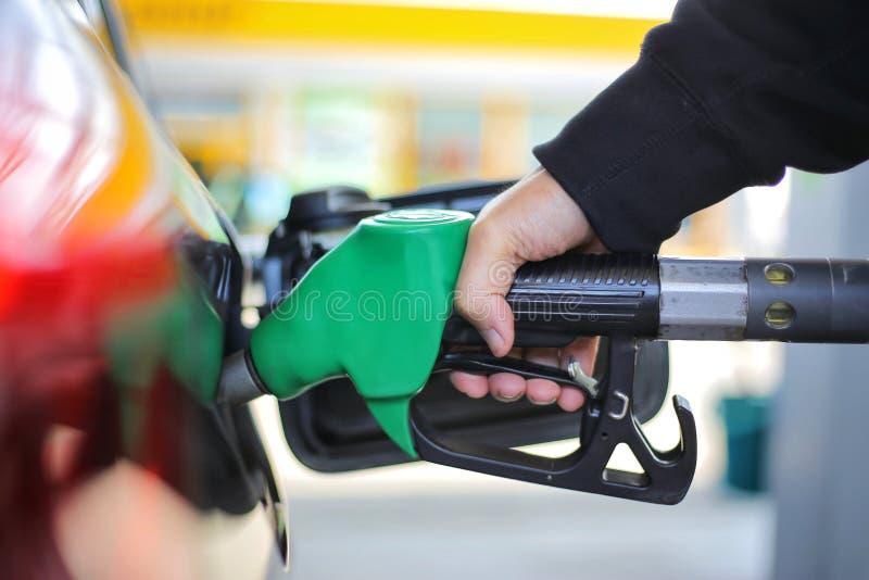 是的手的关闭拿着绿色汽油燃料喷嘴和积土黑汽车汽油箱在全球性矿物燃料的加油站概念的 库存照片