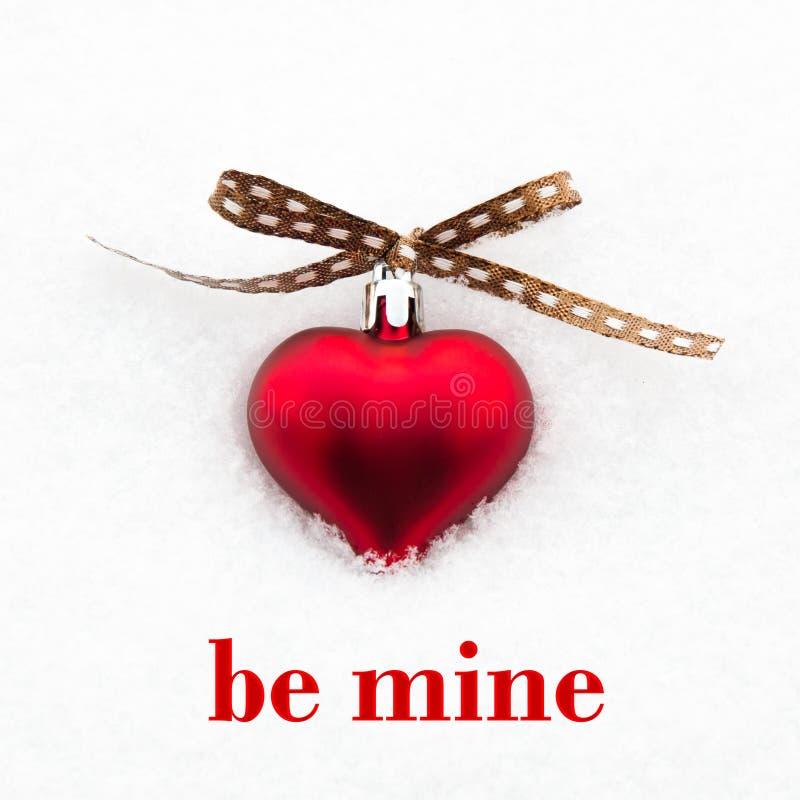 是矿与红色心脏的贺卡在雪 库存照片