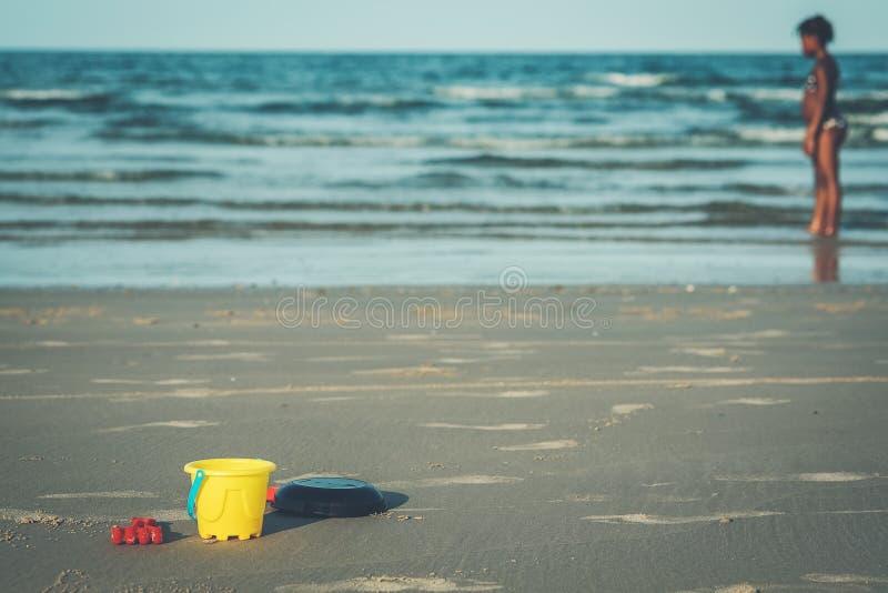 是空的在与孩子的阴影的沙子和海作为背景的玩具、桶和铁锹 免版税库存照片