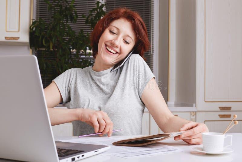 是红头发人快乐的妇女繁忙的与工作,收到在巧妙的电话的订单,做在螺纹笔记本的笔记,高兴有许多力 库存图片
