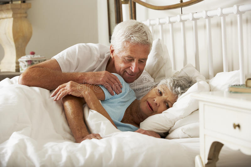 是老人的尝试富感情的往妻子在床上 库存照片