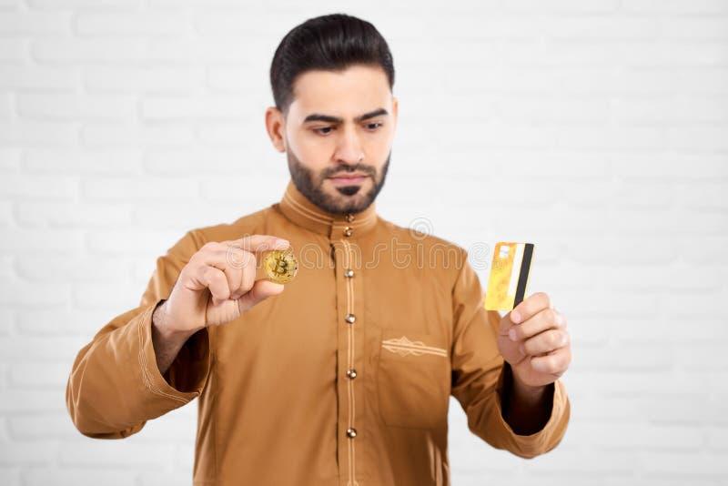 是英俊的穆斯林严肃的,当看信用卡和拿着金黄bitcoin时 免版税库存图片