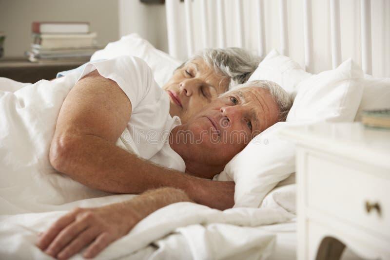 是资深妇女的尝试富感情的往丈夫在床上 库存图片