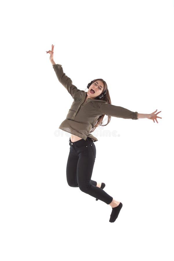 是跳舞和跳,当听到音乐时有耳机的女孩 免版税库存照片