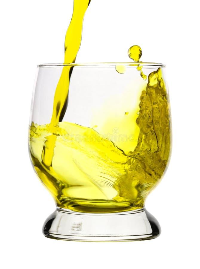 是饮料玻璃倾吐的飞溅黄色 免版税库存图片