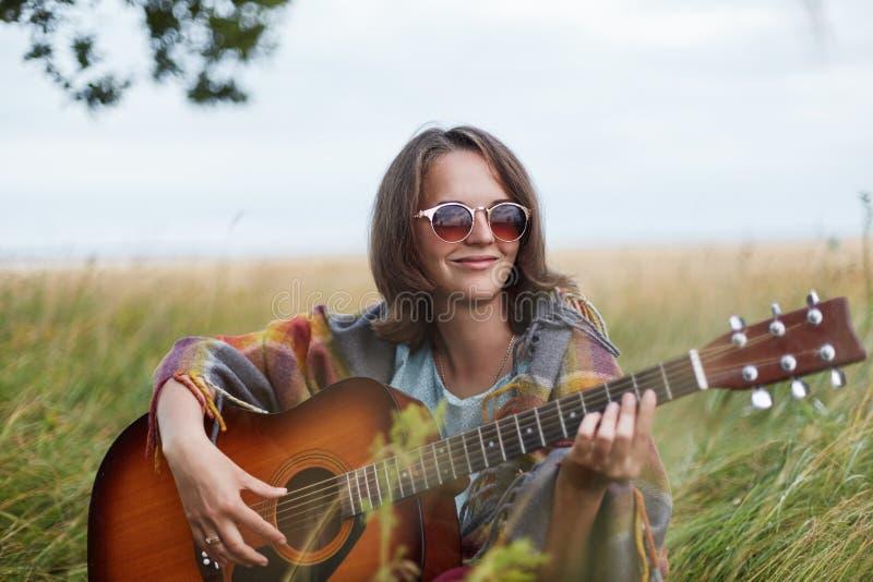 是高兴的女性单独的与弹吉他的自然记住宜人的片刻在她的生活中 相当少妇佩带的太阳镜 免版税库存图片