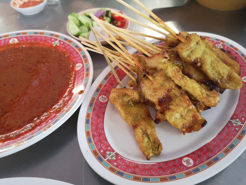 是黄瓜切片和葱在醋食物的猪肉Satay用花生调味汁和腌汁 免版税库存图片
