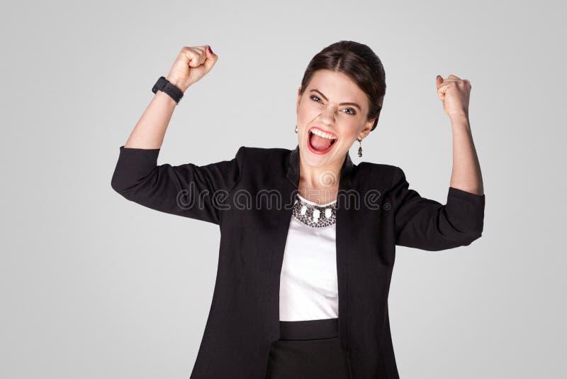 是,我赢取!幸福乐观女实业家欣喜胜利 免版税库存图片