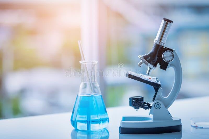 显微镜和烧杯在桌上在实验室 科学化学 库存照片