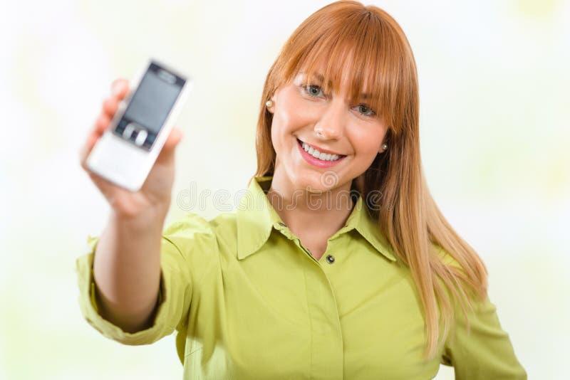 显示一个手机的美丽的女孩 免版税库存图片