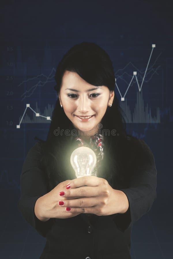 显示一个明亮的电灯泡的成功的女实业家 库存图片