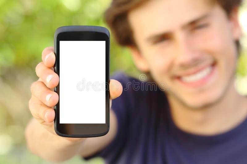 显示一个空白的手机屏幕的愉快的人室外 免版税图库摄影
