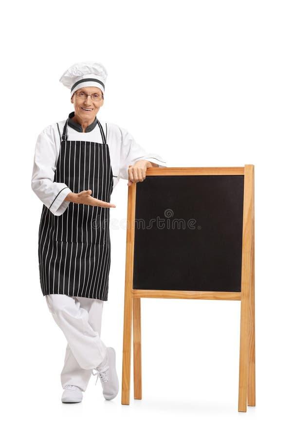 显示一个空白的黑板的厨师的全长画象 库存照片