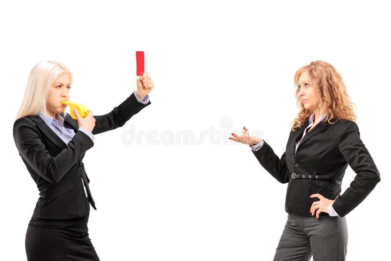 显示一个红牌的女实业家对另一名女实业家 免版税库存照片