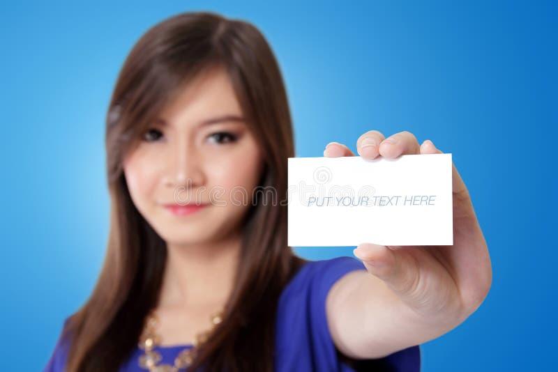 显示一张空白的白色卡片的年轻亚裔妇女 免版税库存照片