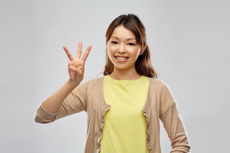 显示三个手指的微笑的亚裔妇女 免版税图库摄影
