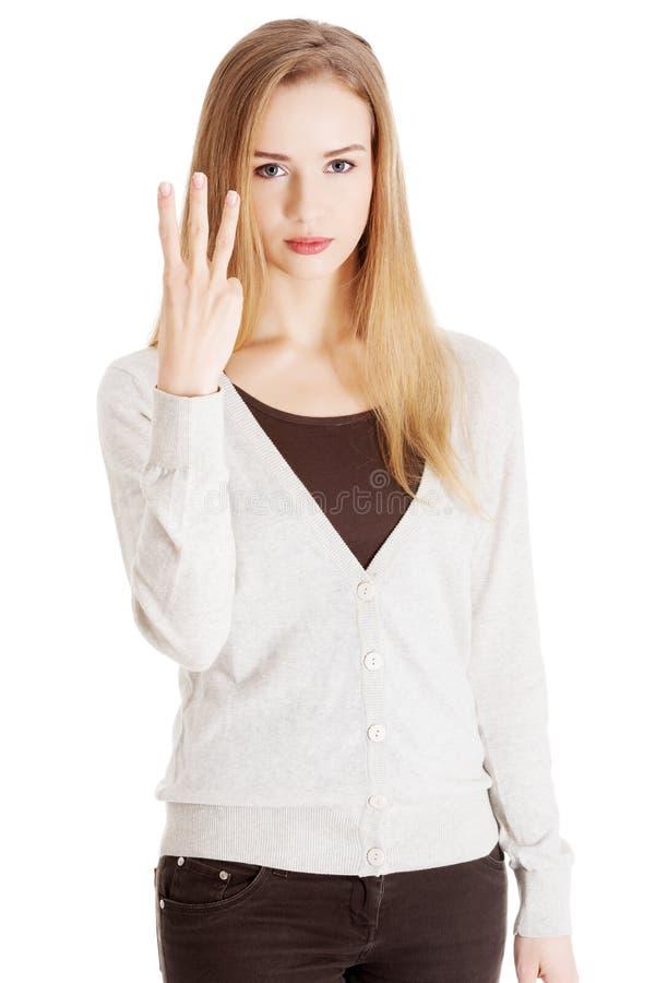 显示三个手指的美丽的偶然妇女。 图库摄影