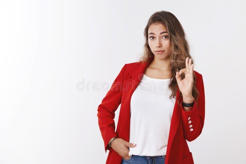 显示不坏姿态的女孩 做ok好标志的被打动的女性同事看起来恭敬检查令人敬畏 库存图片