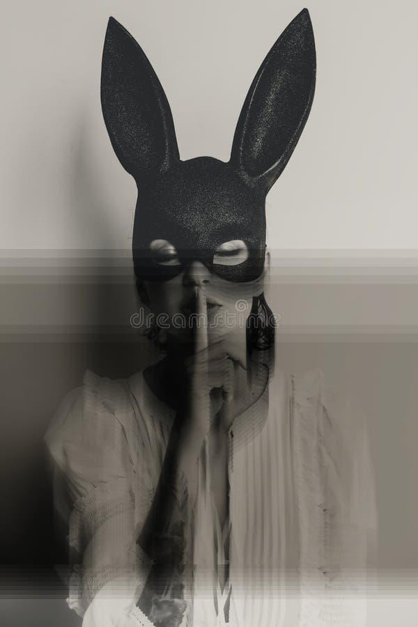显示与她的兔宝宝面具的年轻可爱的妇女安静的标志 免版税库存图片