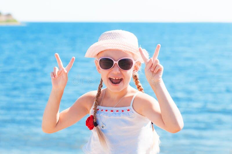 显示与手指的女孩标志胜利临近海 免版税图库摄影