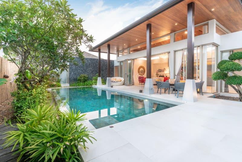 显示与绿叶庭院的家或房子外部设计热带水池别墅 免版税库存照片