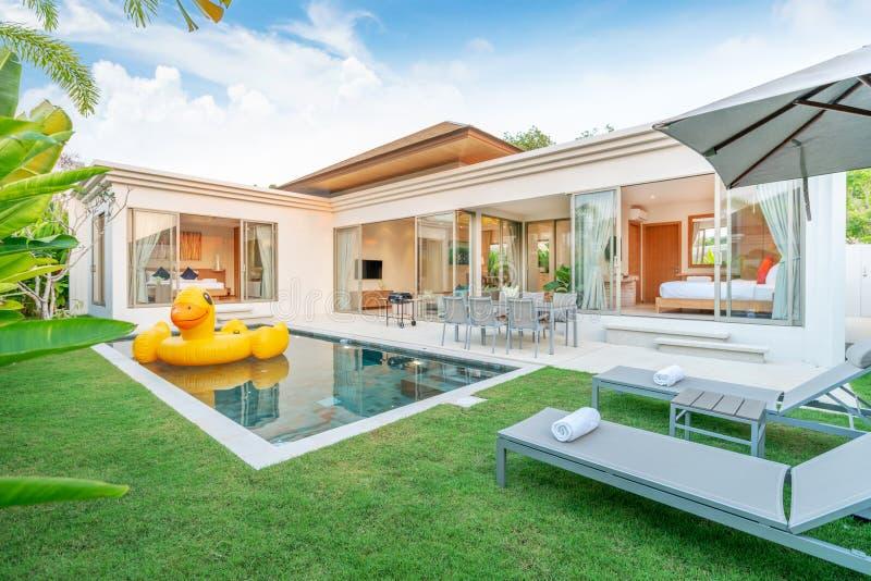 显示与绿叶庭院,太阳床,伞,水池毛巾的热带水池别墅和漂浮鸭子的家或房子外部设计 免版税库存图片
