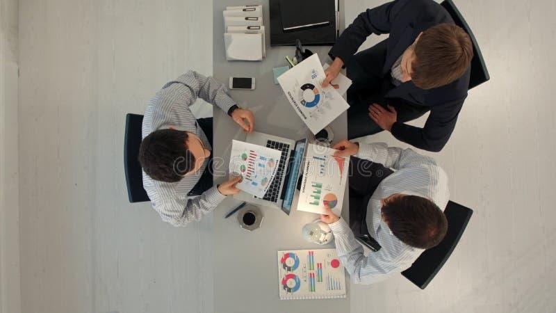 显示与膝上型计算机和片剂个人计算机计算机的创造性的队图坐在桌上在办公室 顶视图 免版税库存图片