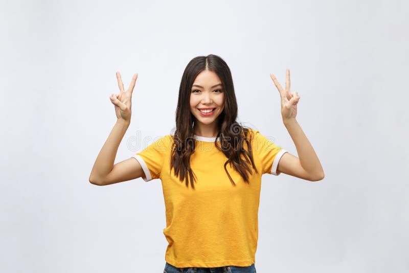 显示两个手指或胜利姿态与空白的copyspace区域的愉快的年轻亚裔妇女文本的,画象美丽 库存照片