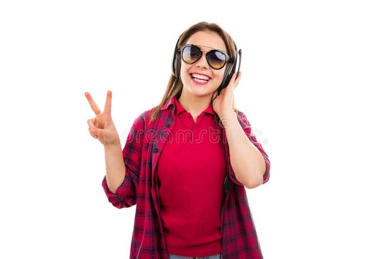 显示两个手指的太阳镜和耳机的妇女 免版税库存图片