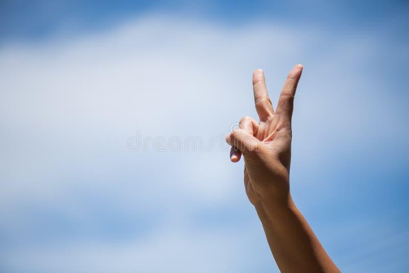 显示两个手指的妇女手当胜利标志 库存照片
