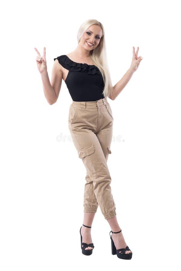 显示两个手指赢得或胜利姿态的愉快的嬉戏的年轻白肤金发的女孩 免版税库存照片