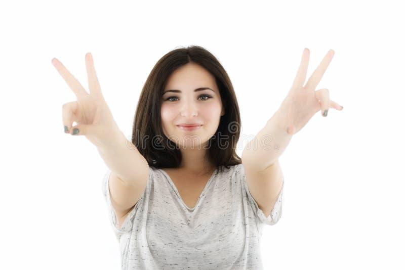 显示两手指或victo的愉快的微笑的美丽的少妇 库存照片