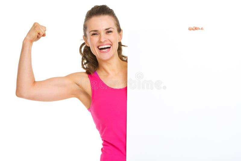 显示二头肌和空白的广告牌的健身妇女 免版税库存照片
